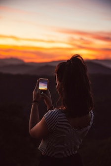 Voyageur prenant une photo du coucher du soleil