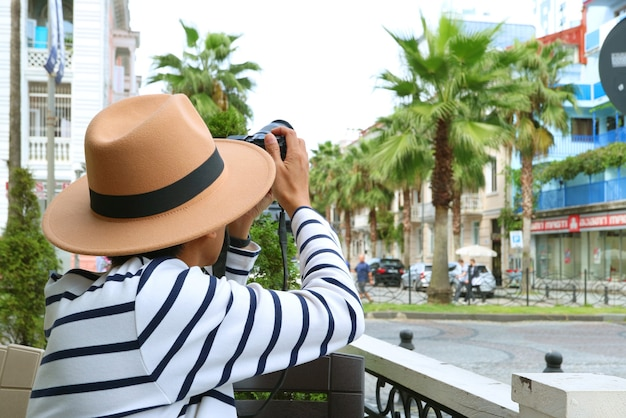 Voyageur prenant des photos depuis le coin salon extérieur avec vue sur la ville en arrière-plan