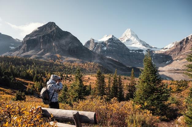 Voyageur prendre une photo avec le mont assiniboine dans la forêt d'automne au parc provincial