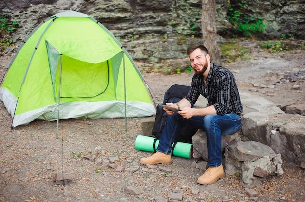 Voyageur près d'une tente avec une tablette le soir.
