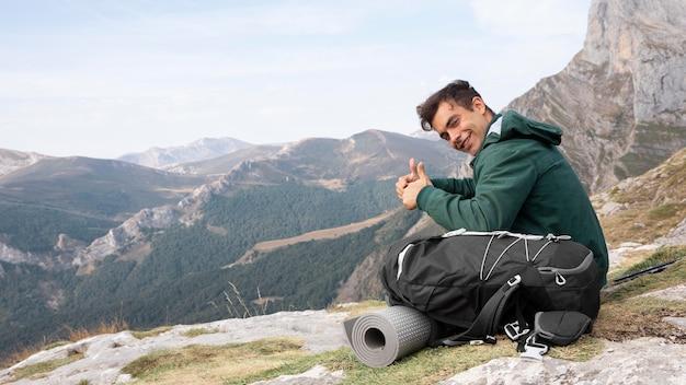 Voyageur en randonnée en montagne tout en ayant l'essentiel dans un sac à dos