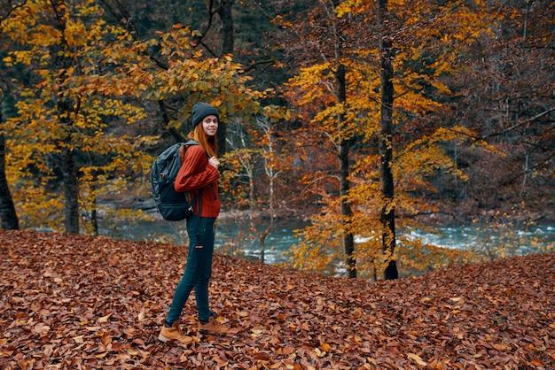Un voyageur avec un sac à dos se promène dans le parc dans la nature près de la rivière en automne