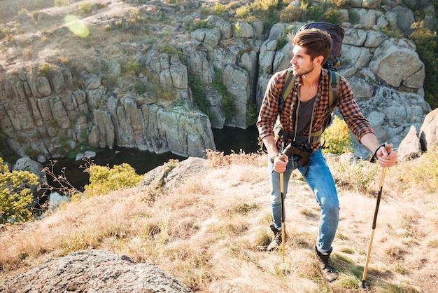 Voyageur avec sac à dos se tient près du canyon à la recherche de suite