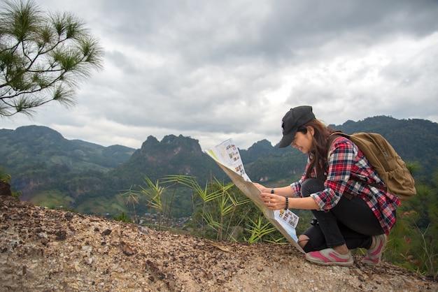 Voyageur avec sac à dos vérifie la carte pour trouver les directions dans la région sauvage