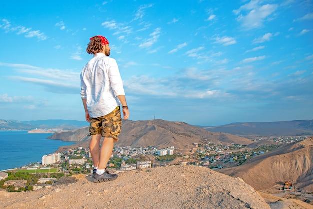 Un voyageur se tient au sommet d'une montagne, admirant le paysage