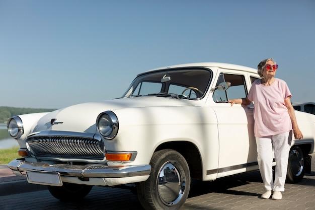 Voyageur senior nid debout à sa voiture