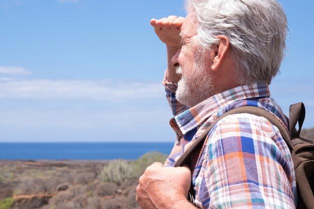 Voyageur senior profitant d'une excursion en plein air marchant entre la montagne et la mer, regardant l'horizon