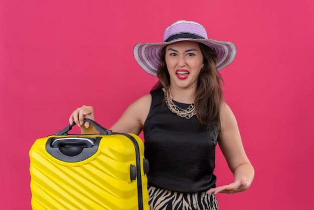 Voyageur squeamish jeune fille portant un maillot de corps noir en chapeau tenant valise et valise points sur fond rouge