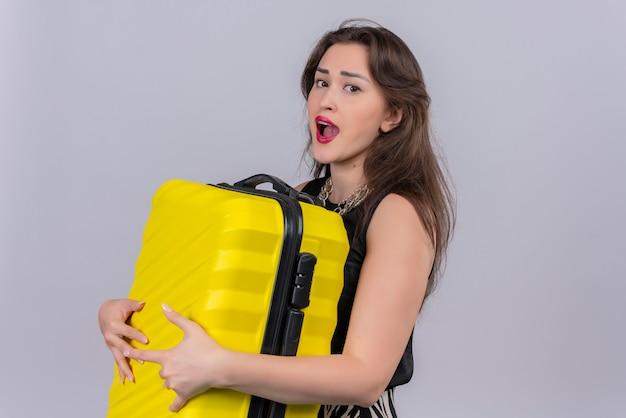 Voyageur surpris jeune fille vêtue d'un maillot de corps noir tenant une valise sur fond blanc