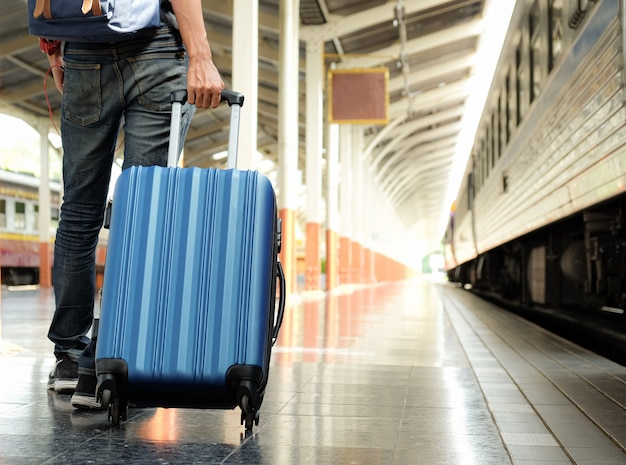 Voyageur avec une valise bleue attend le train.