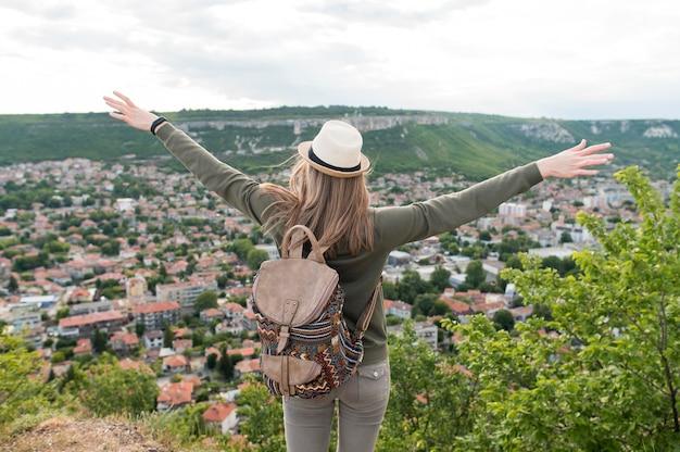 Voyageur vue arrière avec chapeau profitant de vacances