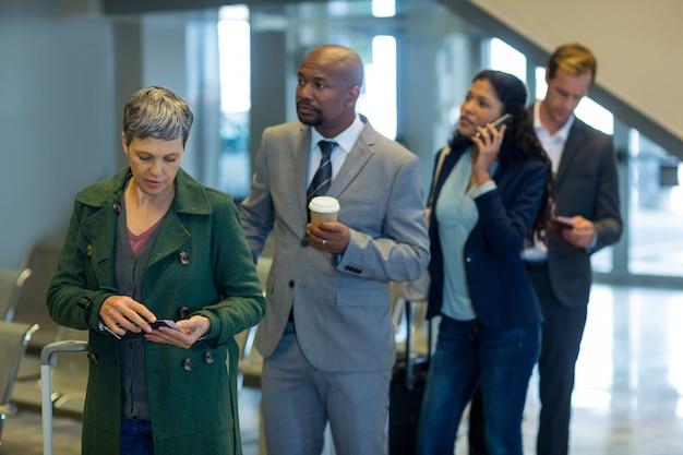 Les voyageurs d'affaires en attente dans la file d'attente