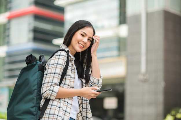 Les voyageurs asiatiques de belle femme utilisent ses téléphones portables.