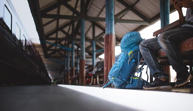 Les voyageurs font de la randonnée et sont assis seuls à la gare.