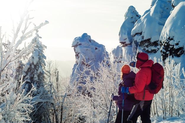 Les voyageurs homme et femme dans les montagnes d'hiver regardent au loin