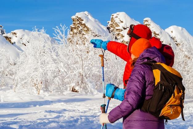 Voyageurs d'homme et de femme dans les montagnes d'hiver se tenant à proximité