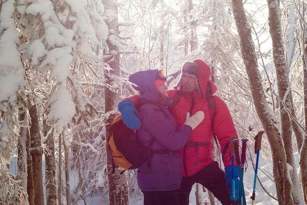 Les voyageurs homme et femme se regardent debout contre le soleil dans la forêt d'hiver