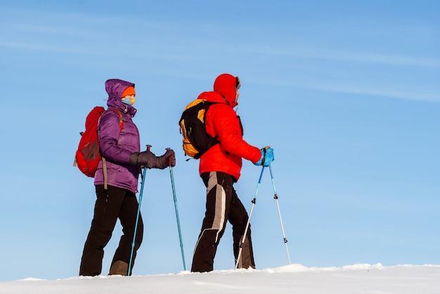 Les voyageurs d'homme et de femme vont en hiver dans la neige contre le ciel