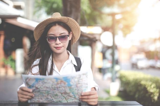 Voyageurs jeune femme avec sac à dos à la recherche d'une carte à la capitale. journée du tourisme