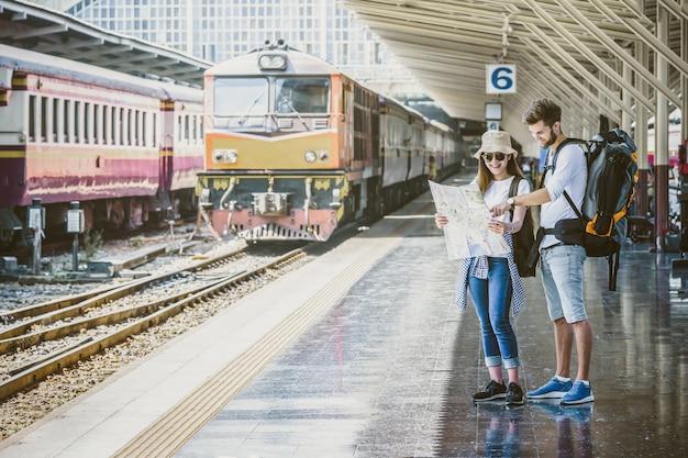 Les voyageurs multiethniques regardent la carte à la gare