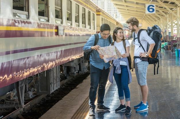 Les voyageurs multiethniques regardent le train et tiennent la carte avec bonheur