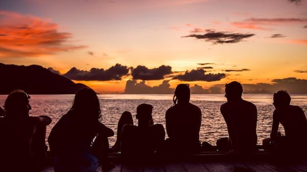 Les voyageurs, les plongeurs se détendre à la jetée au coucher du soleil, l'île de kri. raja ampat, indonésie, papouasie occidentale.