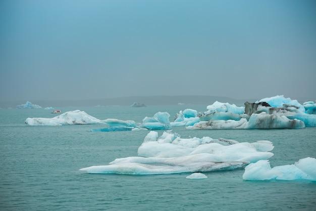 Voyageurs prennent un bateau pour voir la glace flottante dans les icebergs de l'océan dans la lagune du glacier de jokulsarlon, islande