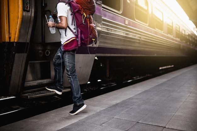 Les voyageurs sont sac à dos et montent dans le train.