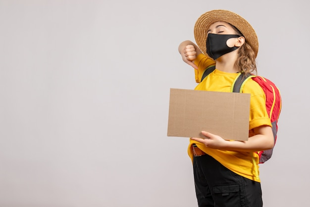 Voyageuse béante vue de face avec sac à dos tenant du carton