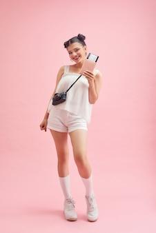 Voyageuse détenant un passeport avec billet. portrait de fille heureuse souriante sur rose.