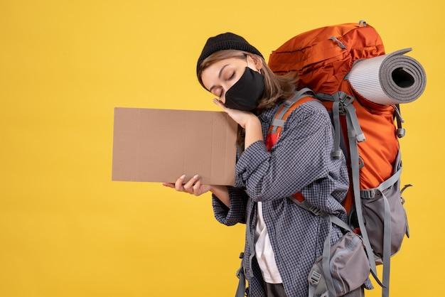 Voyageuse endormie avec masque noir et sac à dos tenant du carton