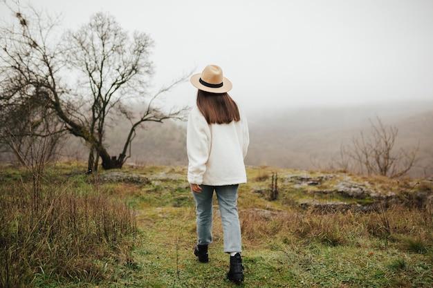 La voyageuse est impatiente de profiter de la vue imprenable sur les montagnes et la vallée. porte une tenue élégante.