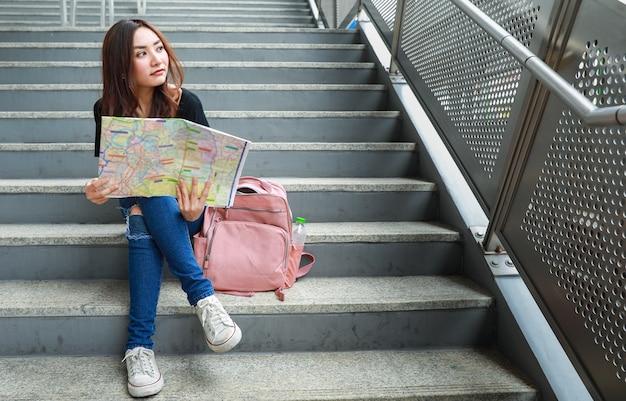 Voyageuse ethnique réfléchie assise dans les escaliers avec une carte papier et détournant les yeux. concept de voyage et de communication de la vie en ville