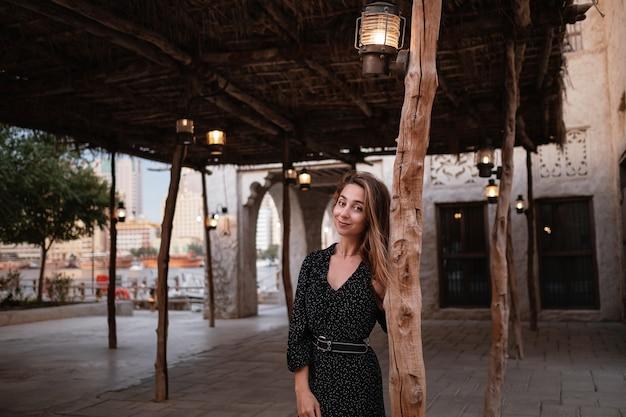 Voyageuse heureuse vêtue d'une robe noire marchant dans les rues d'une vieille ville ou d'un village arabe au milieu du désert. lampes à huile arabes traditionnelles dans la rue al seef dubai