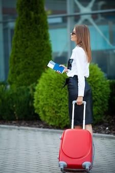 Voyageuse marchant avec leurs bagages près de l'aéroport