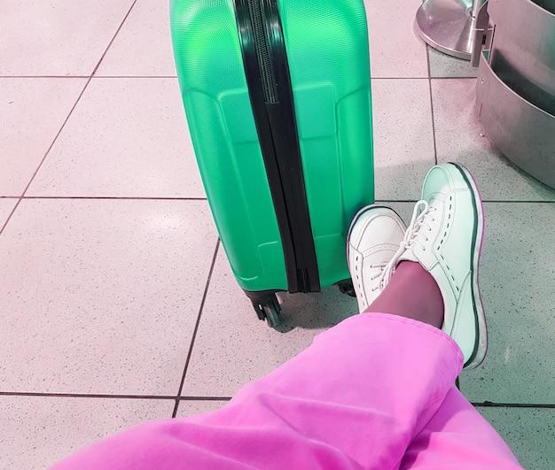 Une voyageuse méconnaissable en pantalon rose et baskets blanches, assise dans une pose détendue, les pieds placés à côté d'une valise verte, attendant un voyage