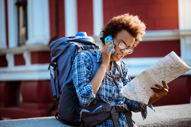 Voyageuse avec sac à dos parlant au téléphone, regardant la carte.
