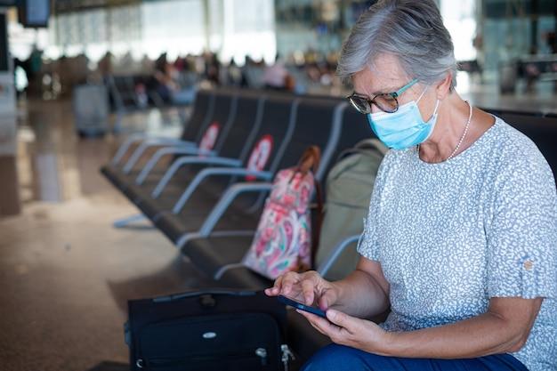 Voyageuse senior assise à l'aéroport avec des bagages à l'aide d'un téléphone portable en attente de départ du vol. concept de coronavirus et de liberté