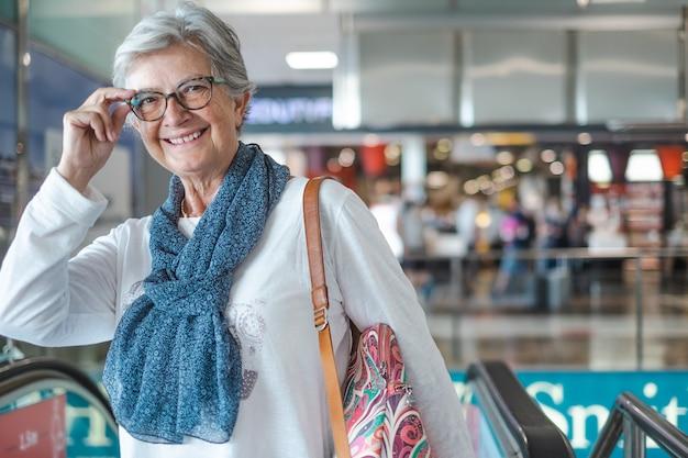 Voyageuse senior dans la zone de l'aéroport avec des bagages en attente de départ du vol. jolie dame aux cheveux blancs souriante regardant la caméra