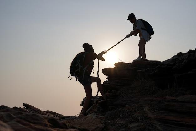 Une voyageuse tire la main de son amie par le bas. idées de réussite, de travail d'équipe et de leadership.