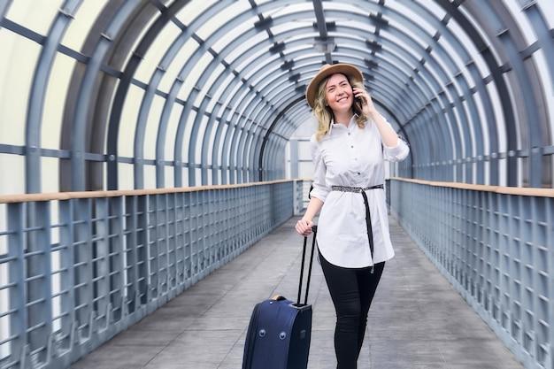 Une voyageuse avec une valise souriante se promène le long de la galerie couverte, parle par téléphone