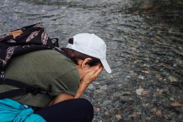Une voyageuse vêtue d'une casquette blanche avec un sac à dos se lave le visage avec de l'eau propre et fraîche de la rivière