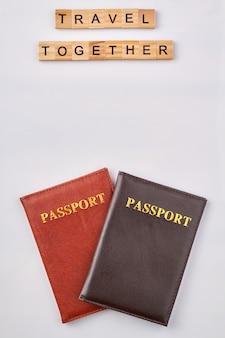 Voyagez ensemble en blocs de lettres en bois. passeports rouges et noirs sur fond blanc.