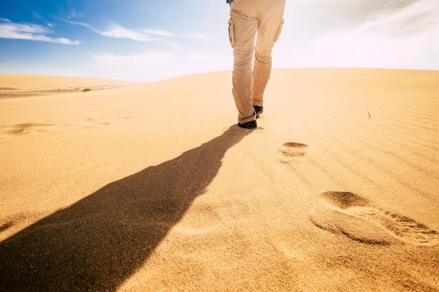 Voyagez et explorez le concept de personnes avec l'homme vu de l'arrière marchant dans le sable des dunes du désert seul sous le coucher du soleil