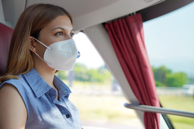 Voyagez en toute sécurité dans les transports en commun. jeune femme avec un masque protecteur kn95 ffp2 regardant par la fenêtre du bus pendant son voyage.