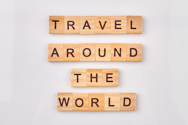 Voyagez à travers le monde. citation inspirante faite avec des blocs de lettres en bois sur fond blanc.