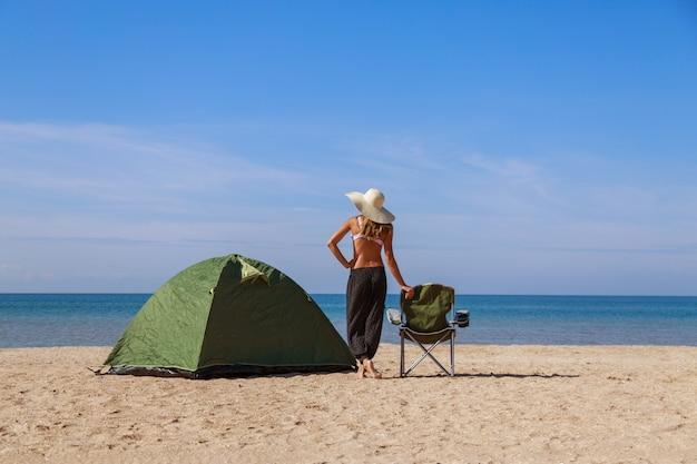 Voyagez vers la mer. camping sur la plage. vacances au bord de l'eau. des hommes et une tente avec une chaise touristique sur le sable