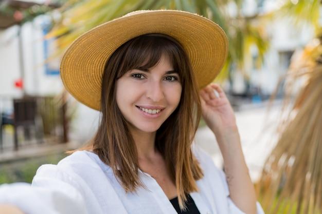 Vportrait d'été de jolie femme brune en chapeau de paille posant en plein air.