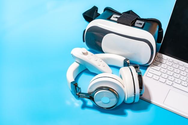 Vr, casque, ordinateur portable sur fond bleu. concept pour vr, jeu, simulation et technologie.