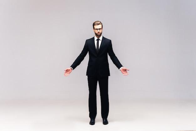 Vraie affaire. prise de vue en studio sur toute la longueur d'un beau jeune homme en costume complet, gardant les mains tendues et regardant la caméra